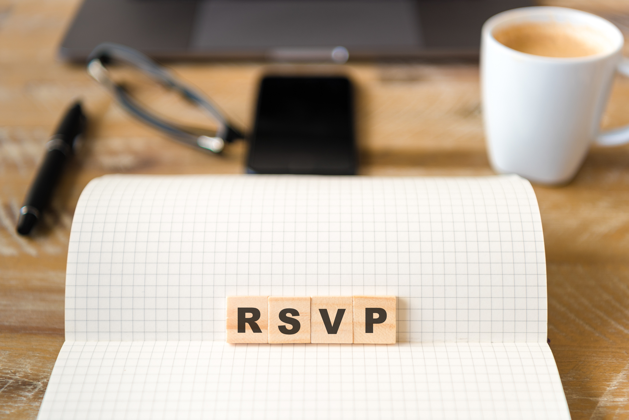 Closeup on notebook over wood table background, focus on wooden blocks with letters making RSVP word
