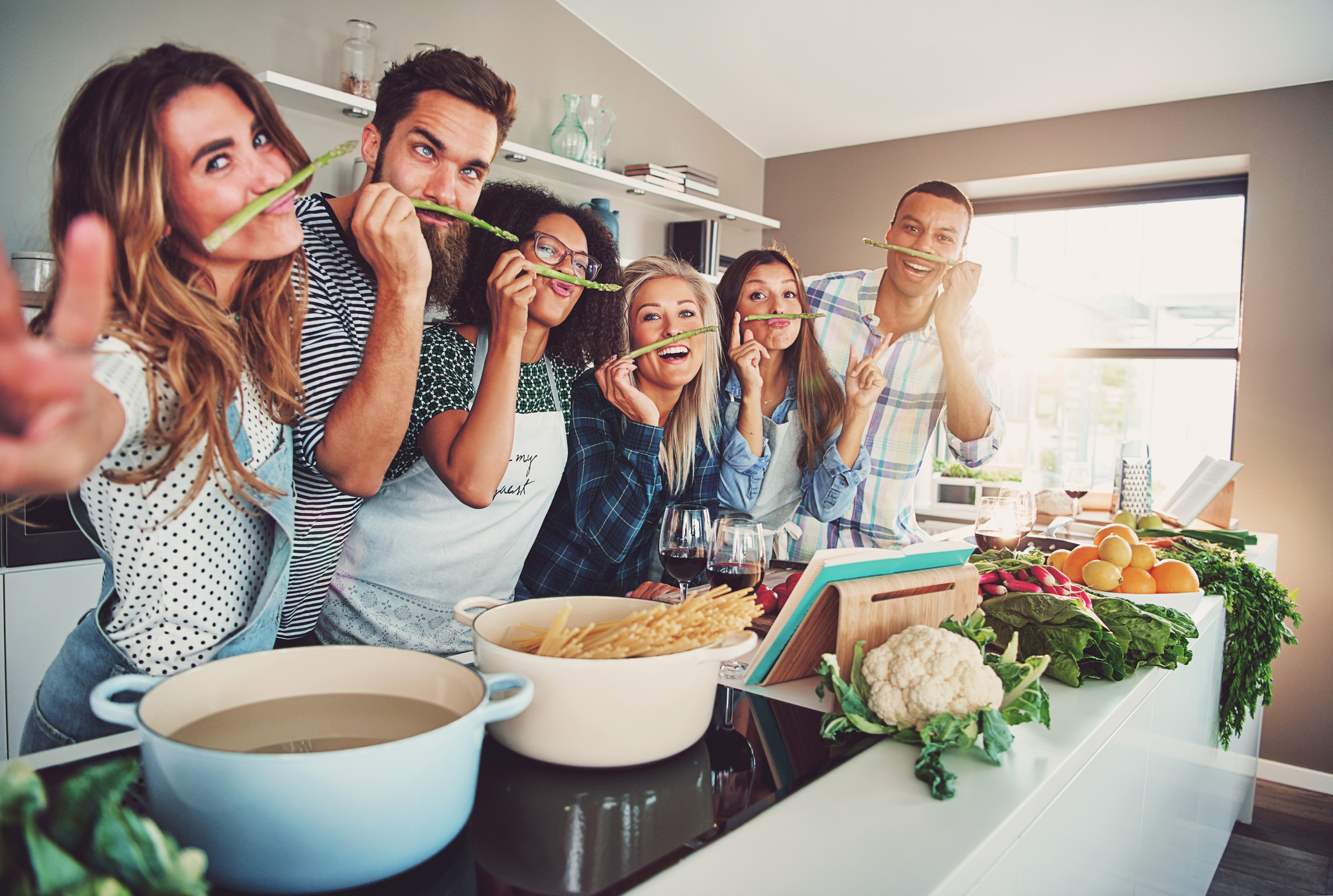 Five friends having a little break to fool around with some asparagus while cooking