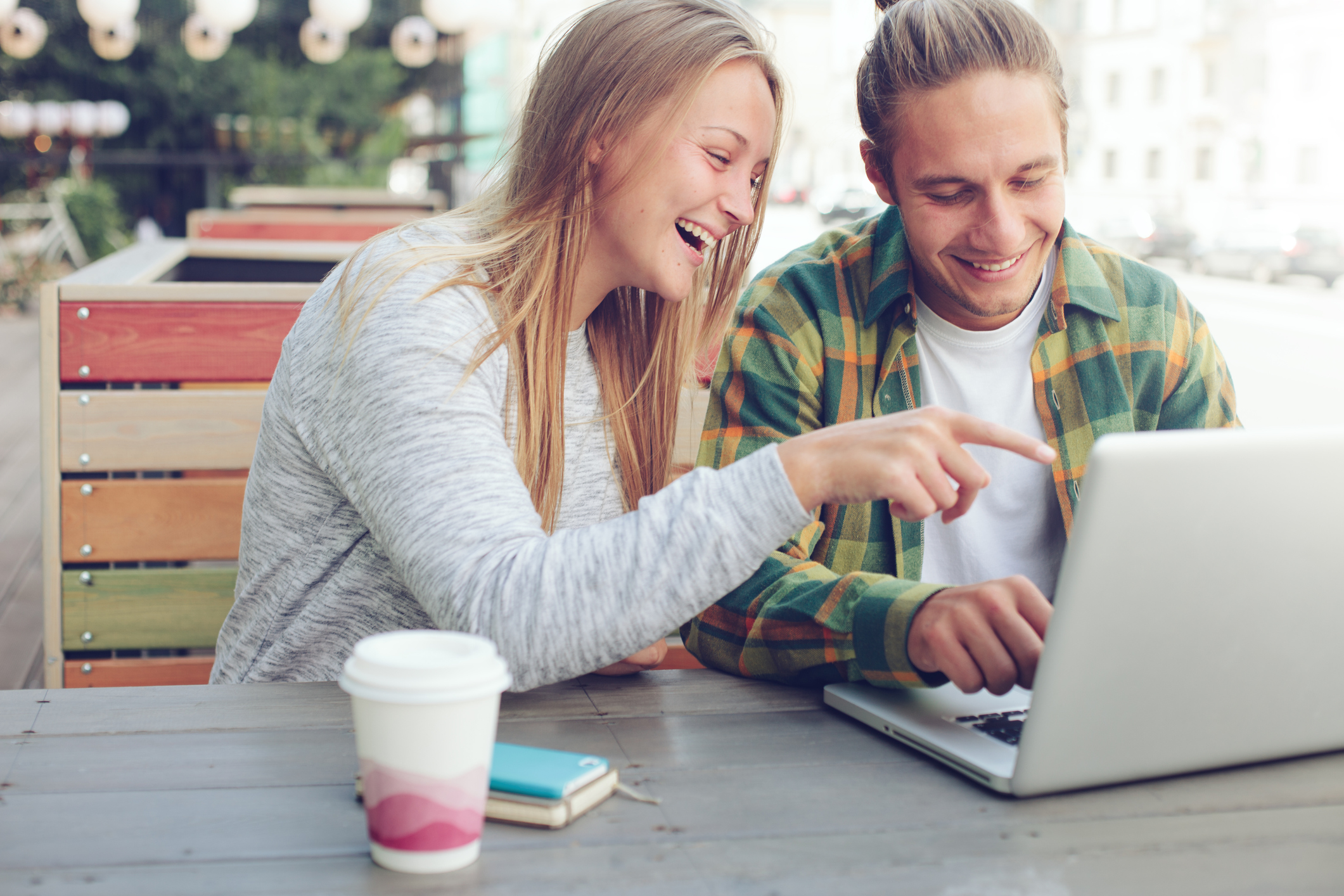 Man and woman sitting in street cafe with laptop