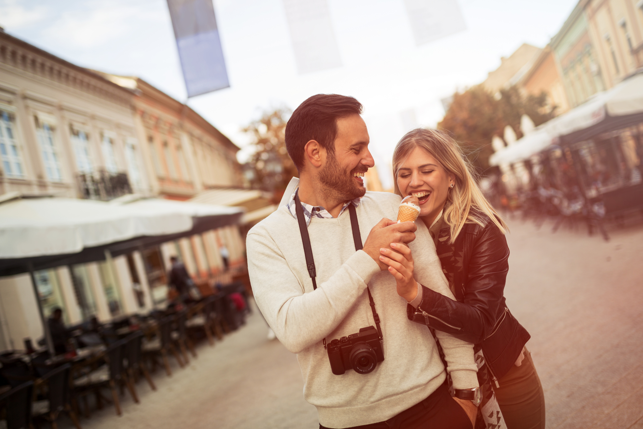 Tourist couple sharing ice cream outdoors and smiling