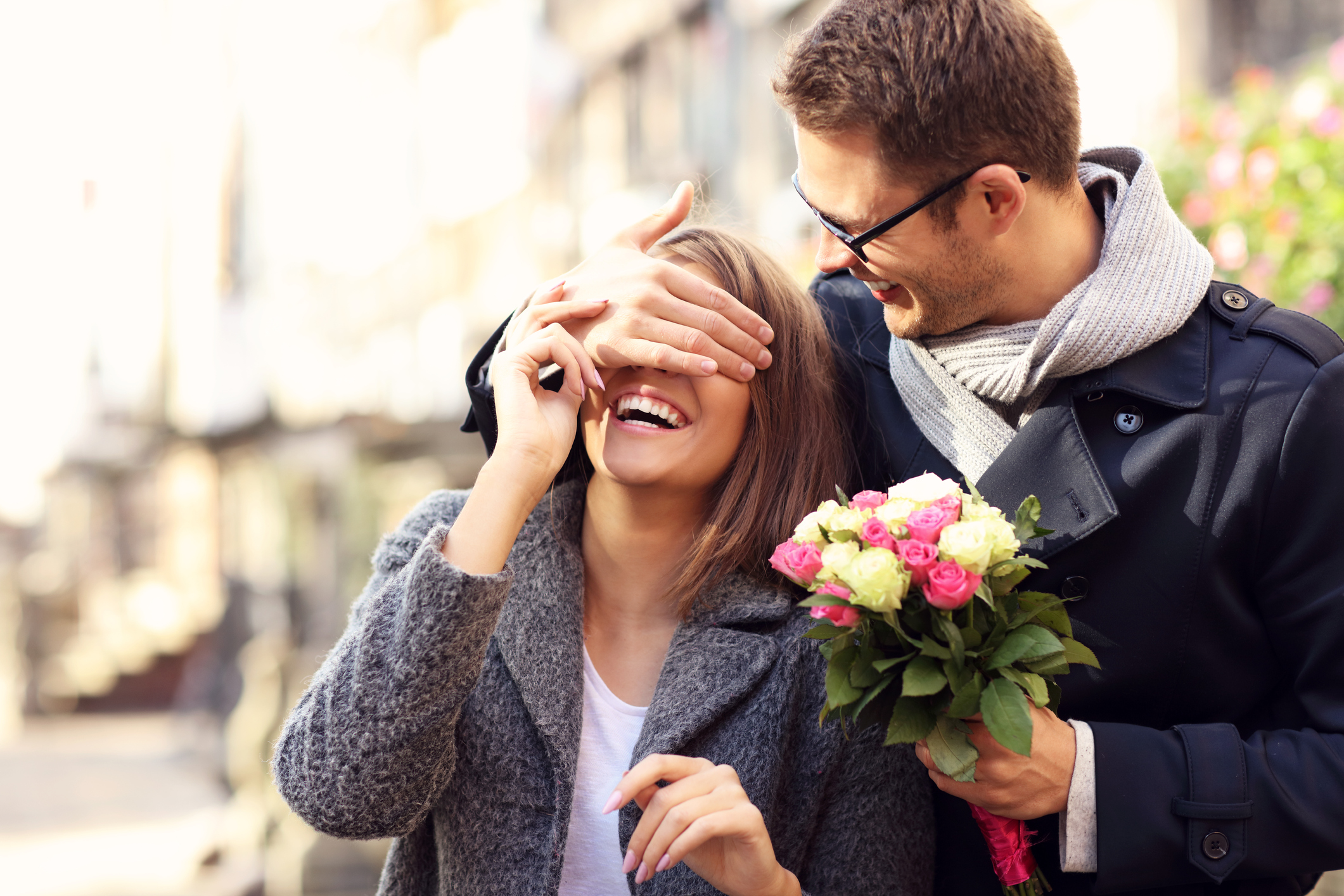 Picture of young man surprising woman with flowers