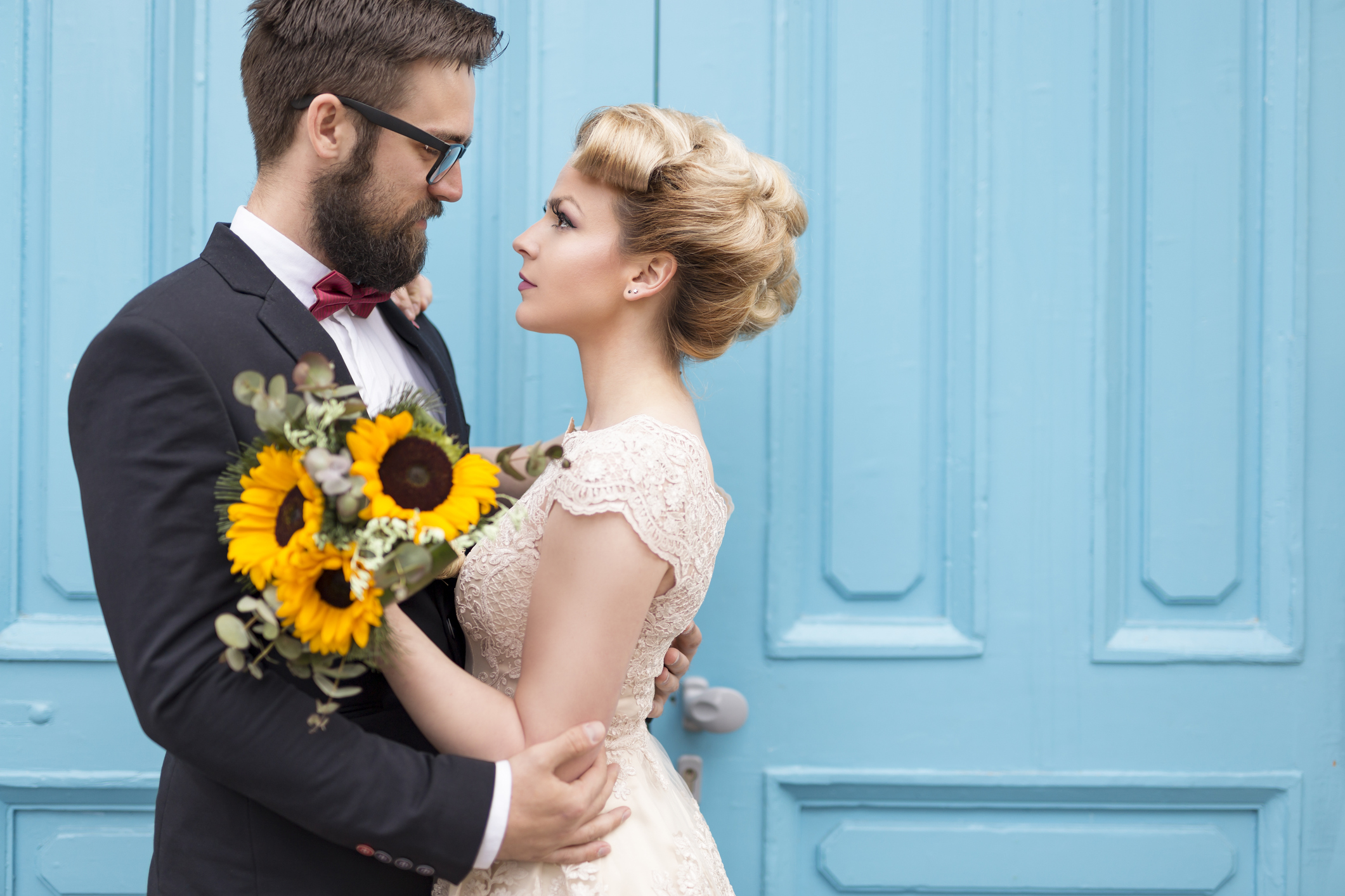 Newlywed couple standing next to a blue retro wooden door, holding a sunflower wedding bouquet and looking at each other