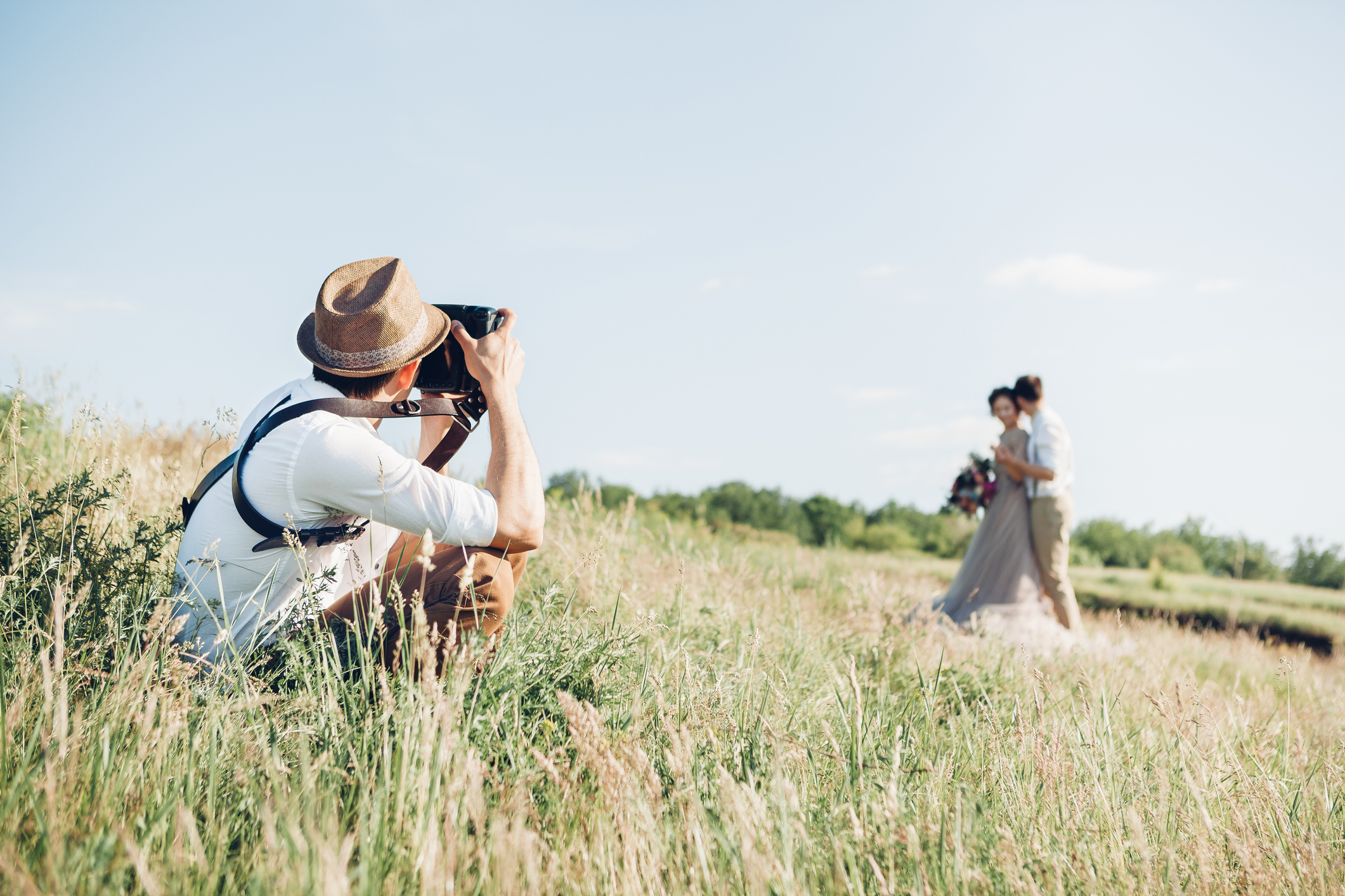 wedding photographer takes pictures of bride and groom in nature in summer, fine art photo