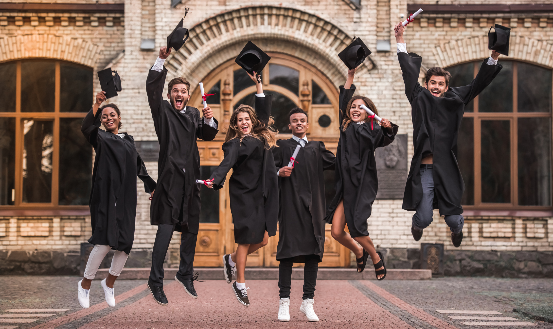 Successful graduates in academic dresses are holding diplomas, looking at camera and smiling while jumping for the photo outdoors