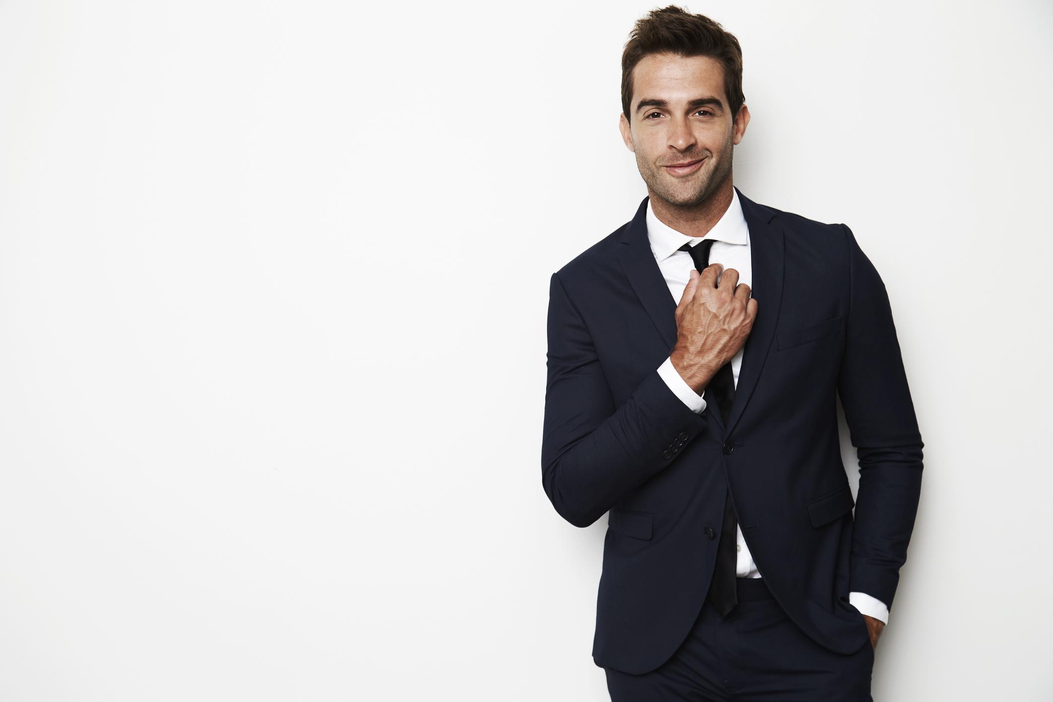Handsome businessman adjusting tie, smiling