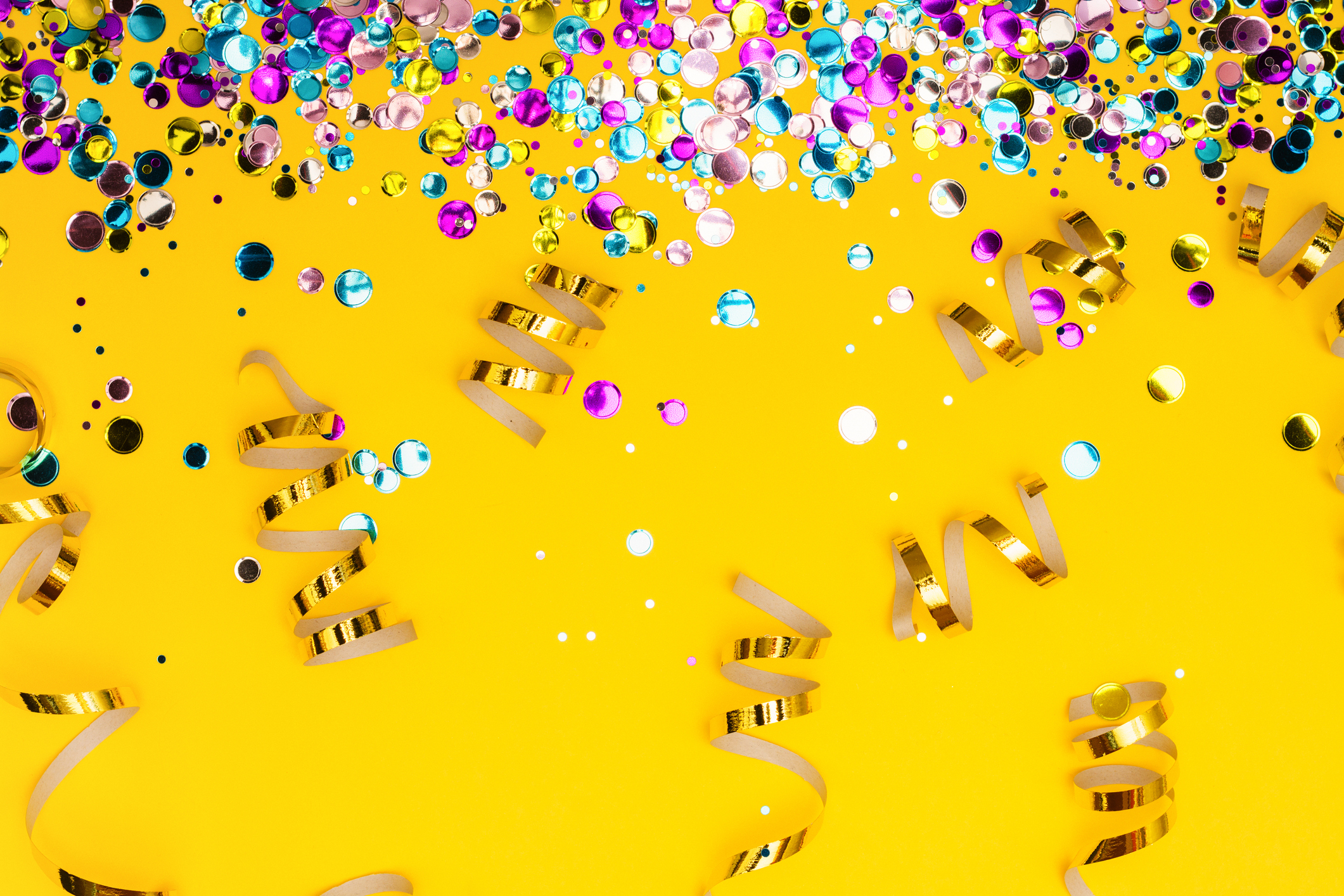Colorful confetti and golden coiled streamers on yellow background. Festive party or carnival border. Copy space