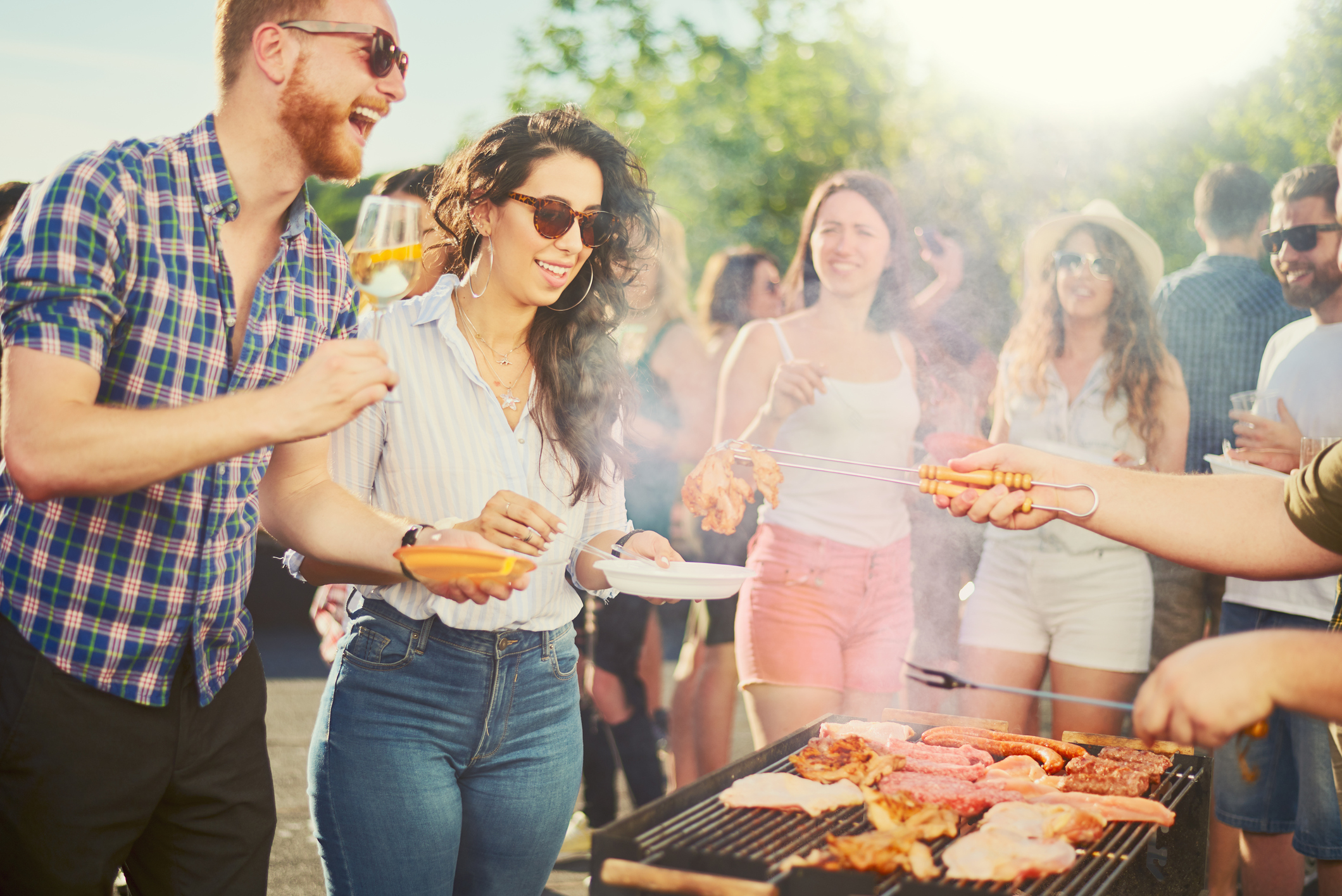 Small group of people standing around barbecue grill at outdoor party