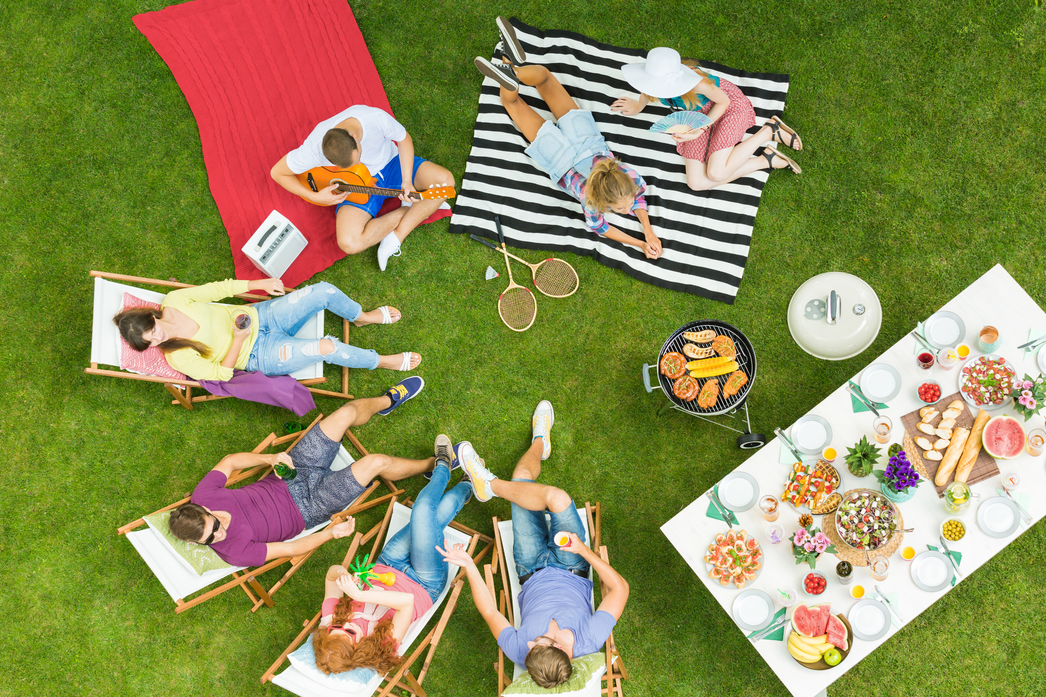 Top view of group of young friends having summer barbecue party in the backyard with grill and table full of delicious food