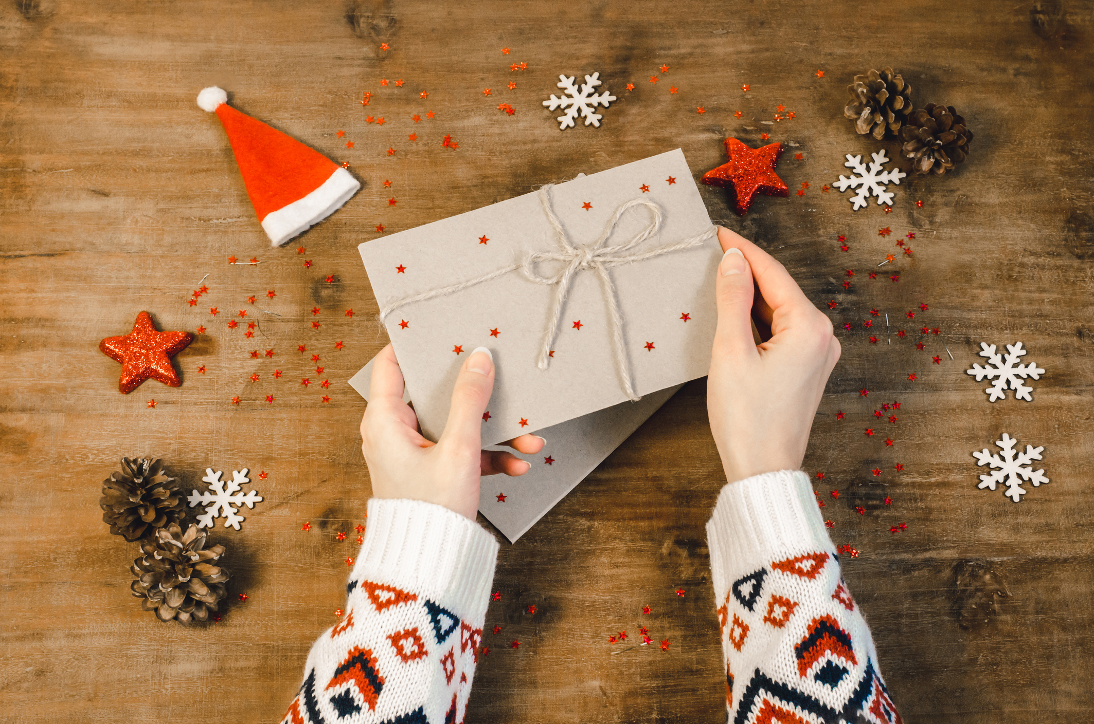 Stylish christmas flat lay with woman hands hold (open) post card letter. Holiday celebration concept woman hands in a knitted sweater writing letter.